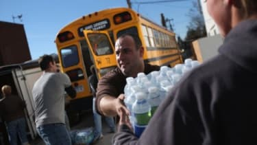Volunteers unload water at an aid distribution center at the Long Beach Ice Arena in New York on Nov. 4.