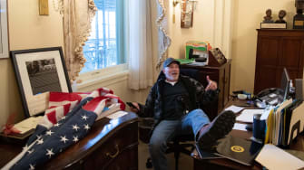 A supporter of US President Donald Trump sits inside the office of Speaker of the House Nancy Pelosi.