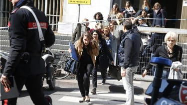 People flee from the Milan courthouse.