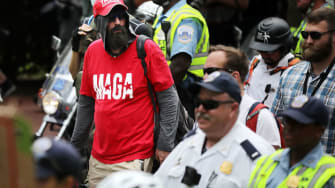 A white supremacist rally participant surrounded by police officers.