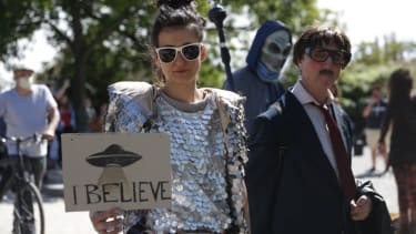 """A woman holds a banner with an UFO painted on it and reading """"I believe"""" as another protester dressed up as alien walks by at a demonstration against conspiracy theorists at Mauerpark, amidst"""