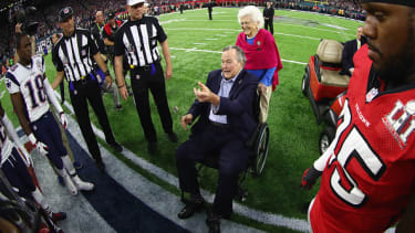 Former President George H.W. Bush assists with the coin toss at the beginning of Super Bowl LI.