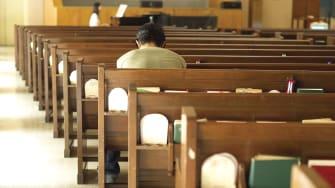 A man prays in an empty church.