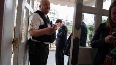A security guard stands at the door of the White House press room.