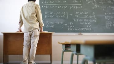 A teacher facing the chalkboard: If this teacher were employed in Arizona's Peoria school district he would not be allowed to wear those sneakers.