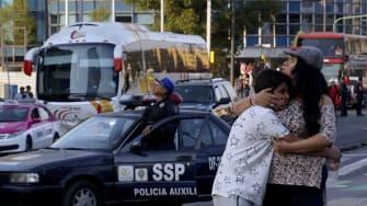 A woman embraces a boy as a powerful earthquake rocks Mexico City on February 16, 2018.