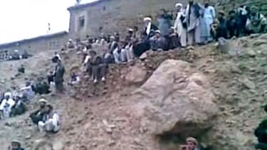 Afghan men stand on a hill moments before a Taliban judge shoots a woman to death, reportedly her punishment for alleged adultery.