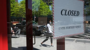 People walk through a shuttered business district in Brooklyn on May 12, 2020 in New York City