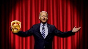 Former Vice President Joe Biden holds a tragedy mask on a stage.