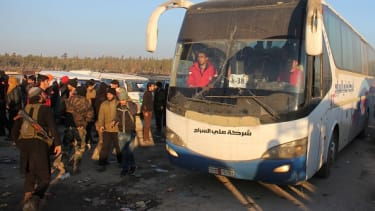 Buses carry evacuees out of eastern Aleppo on Monday.