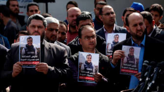 Palestinian journalists carry a portrait of journalist Yasser Murtaja, during his funeral in Gaza City on April 7, 2018.