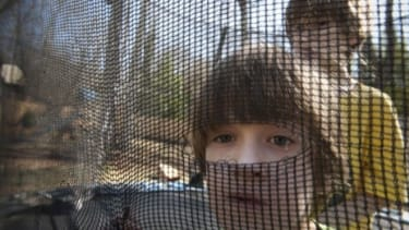 Twins Ben (front) and Sam Schwenker, who were diagnosed with autism at 18 months, play on their trampoline: A new study may help scientists come closer to understanding the disease's origins.