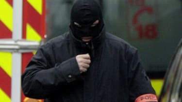 A masked French special intervention police member arrives on the scene during a raid to arrest the suspect in the killing of three children Monday.