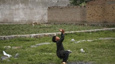 A boy plays with a ball in front of Osama bin Laden's Pakistan compound: Neighborhood kids would not get their balls returned if they were lost in the terrorist's yard.