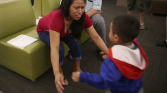 A migrant mother is reunited with her son in Texas