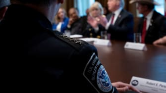 A CBP officer listens to Trump