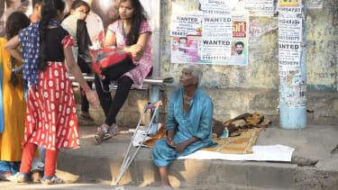 An Indian begger sits on the side of the road in Hyderabad on November 10, 2017.