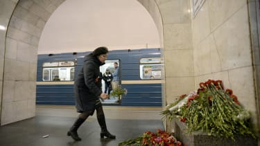 A mourner leaves flowers at a makeshift memorial for the deadly St. Petersburg attack.