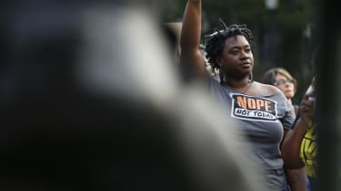 Ericka Robbins, of Birmingham, Ala., holds up her fist during a solidarity rally in Birmingham for the victims in Charlottesville.