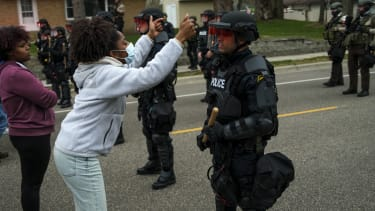 A protester and a police officer in Brooklyn Center