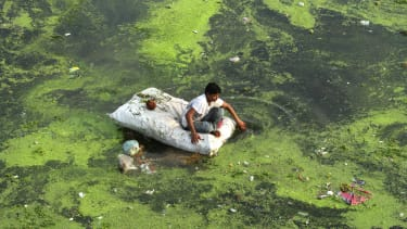 An Indian man sits on a raft in a polluted river