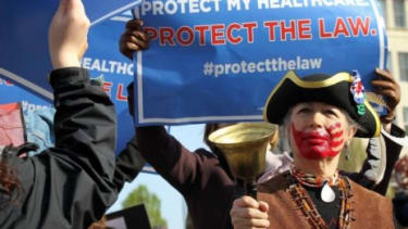 """Tea Party member Susan Clark rings a bell as ObamaCare supporters demonstrate in front of the Supreme Court in March: If the court strikes down the entire law, it would be a """"painful blow"""" fo"""