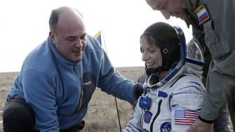 Ground personnel help astronaut Kate Rubinsget out of the Soyuz space capsule