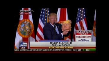 Donald Trump holds up a mask of himself.