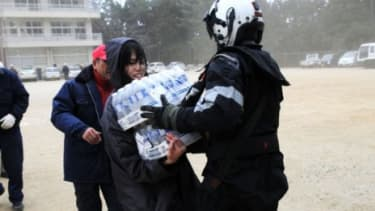 A U.S. naval air crewman delivers bottled water to a Japanese citizen after the earthquake.