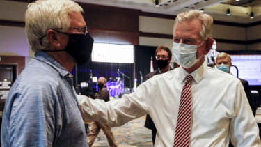Tommy Tuberville, right, speaks with a supporter.