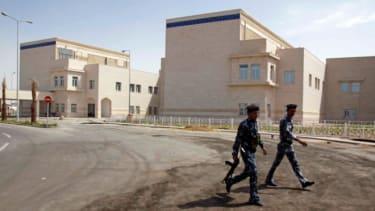 Iraqi police walk past the Basra Children's Hospital, August 12, 2010.