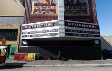 A person walks under a marquis for a closed down Paramount theater