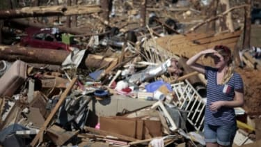 A woman surveys the damage of Thursday's tornados in Tuscaloosa, Alabama, where 900 people have been injured and, unofficially, more than 40 people killed.
