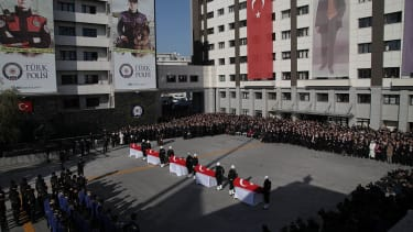 Turkish police officers stand guarded near the flag-draped coffins of police officers killed in yesterday's blast on December 11, 2016 in Istanbul, Turkey