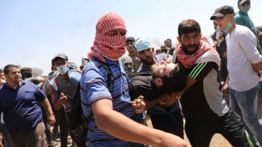 A wounded Palestinian man is rushed to an ambulance.