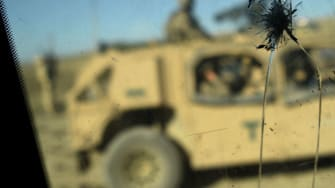 U.S. Army soldiers from NATO are seen through a cracked window of an armed vehicle in a checkpoint in Afghanistan.