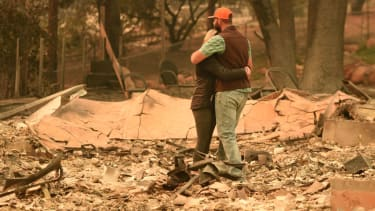 A couple reacts to their home burning down.