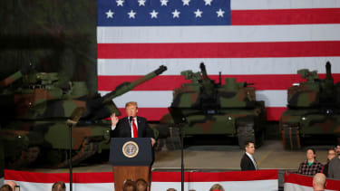 President Trump is flanked by tanks.