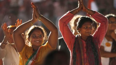 A pair of Indian women practice yoga.