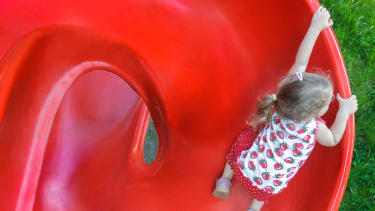 A girl climbs a bright red slide.
