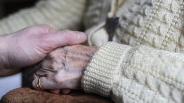 A woman holds her elderly relative's hand.