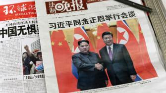 A newspaper shows Kim Jong Un and Xi Jinping.
