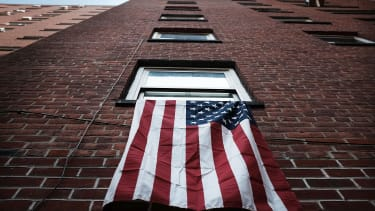 An American flag hangs from a window in an East Harlem public housing complex