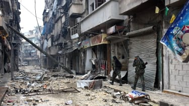 Government forces walk through a neighborhood in Aleppo.