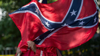 A protestor holds a confederate flag in front of his face.