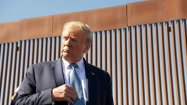 Donald Trump next to the border wall.