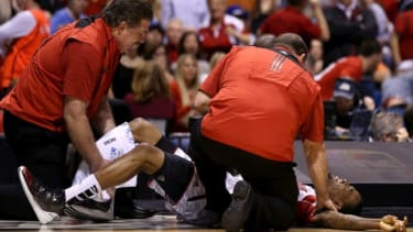 Medics try to calm Kevin Ware after a brutal injury, at Lucas Oil Stadium, March 31.
