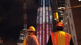 Construction workers look up at the Freedom Tower at the World Trade Center that is patriotically lit in advance of the tenth anniversary.