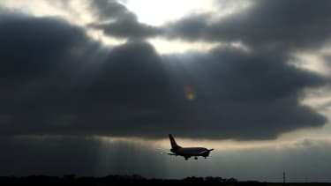 plane flies under dark grey sky