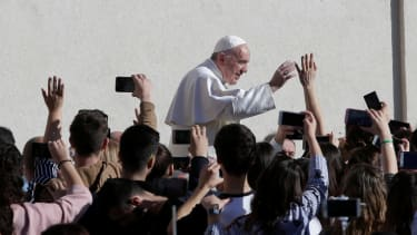 Pope Francis waves to onlookers while arriving at the Vatican.